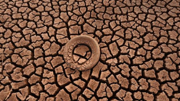 Ein Reifen liegt auf dem ausgetrockneten Boden eines Sees.