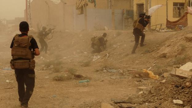 Kämpfe in der westirakischen Stadt Ramadi. Ein IS-Kämpfer hisst die schwarze Flagge der Terrormiliz.
