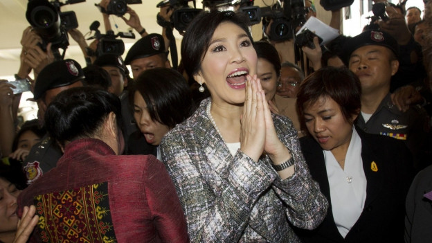 Die thailändische Premierministerin hält die Hände zusammen und scheint zu jubeln, im Hintergrund stehen Menschen und ein halbes Dutzend Fernsehkameras.