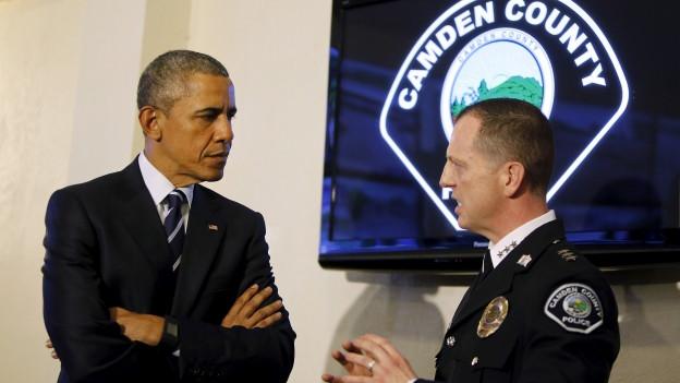 US-Präsident Obama im Gespräch mit einem ranghohen Polizeioffizier, in Hintergrund ein Monitor, auf dem ein Logo mit der Aufschrift «Camden County» zu sehen ist.