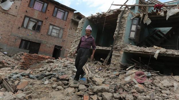 Ein Mann läuft über Trümmer eines eingestürzten Hauses.