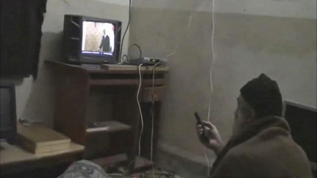 Bin Laden von hinten mit Fernbedienung vor einem Fernseher sitzend.
