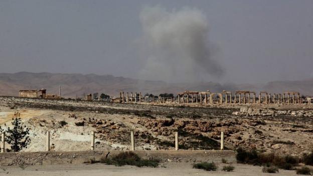 Antike Säulen, im Hintergrund Gefechtsrauch