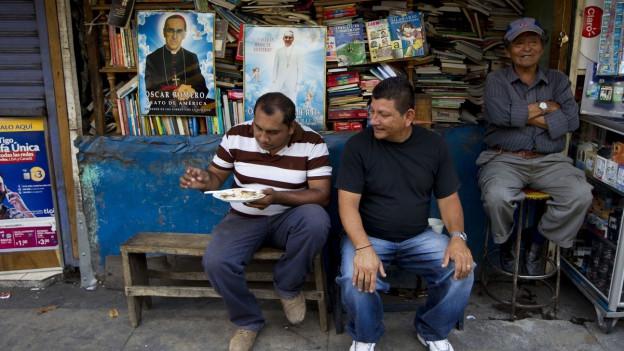Männer sitzen vor einem Stand mit gebrauchten Büchern und Romero-Portraits.