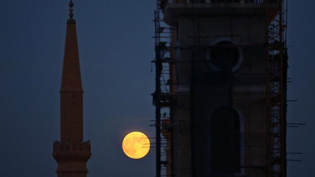 Der Vollmond leuchtet zwischen dem Turm eines Minaretts und einer Kirche in Beirut.