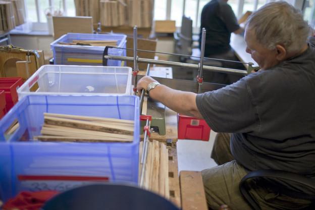 Eine behinderte Person in einer geschützten Werkstatt am arbeiten.