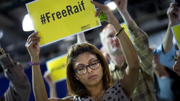 Frau hält Schild mit Aufschrift «Freiheit für Badawi» hoch.