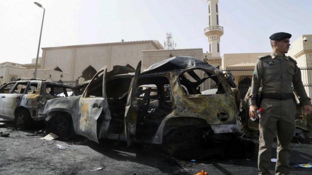Mehrere ausgebrannte Auto und ein Polizist stehen vor der Moschee in Dammam.