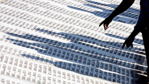 Menschen zeigen auf Namen einer Liste in Gedenken an die Opfer des Krieges.