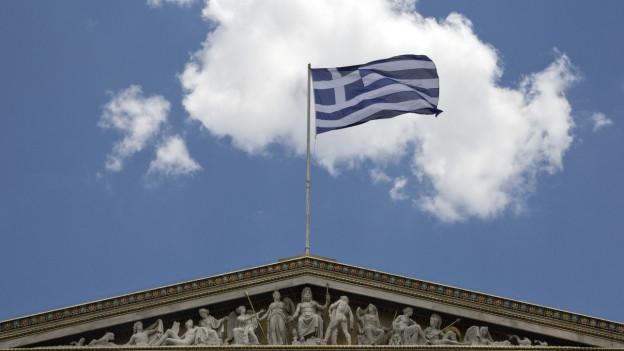 Eine griechische Fahne weht auf dem Dach der Athens Academy.