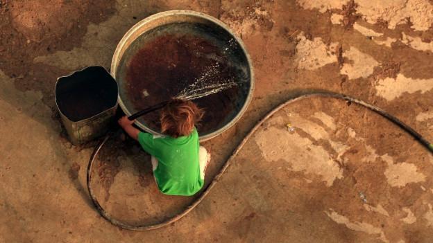 Ein Kind hält einen Schlauch in eine Schale, um diese mit Wasser zu füllen.