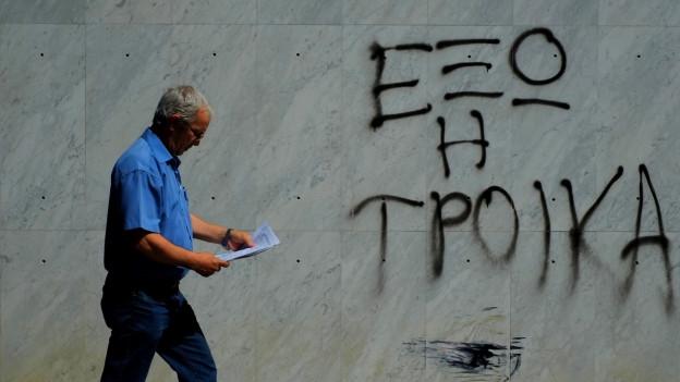 Auf einer Hauswand steht der Spruch «Troika raus», ein Mann läuft daran vorbei.