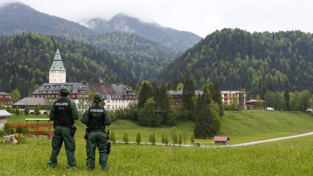 Zwei Polizisten von hinten vor dem Schloss Elmau