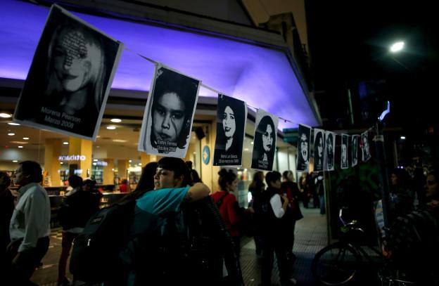 An einer Kundgebung in Buenos Aires umarmen sich zwei Frauen unter Bildern, die Opfer von Frauengewalt zeigen. In Argentinien wird fast jeden Tag eine Frau von ihrem Partner ermordet.