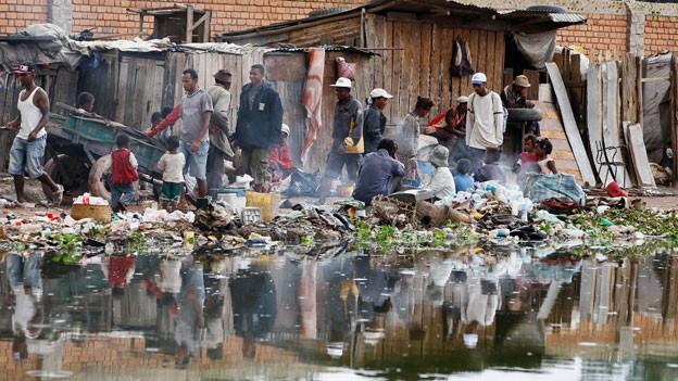 Einwohner entlang eines müllverseuchten Wasserkanals in der Stadt Antananarivo in Madagaskar.