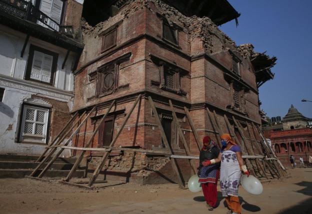Zwei Frauen laufen an einem Haus vorbei, dass seit dem Erdbeben gesichert werden muss.