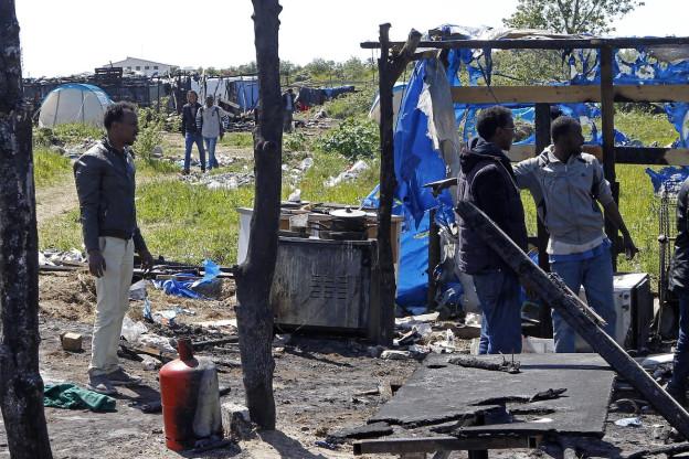 Mehrere Flüchtlinge auf Afrika warten im Flüchtlingslager im französischen Calais auf die Ausreise nach Grossbritannien.