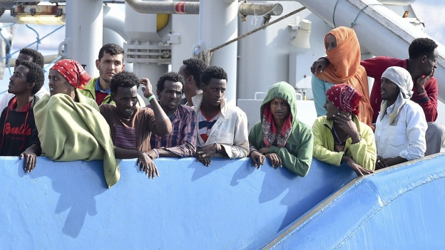 Flüchtlinge aus Afrika stehen an der Reling eines Schiffs.