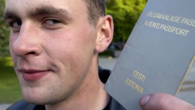 Junger Russe mit estnischem Pass in der Hand.