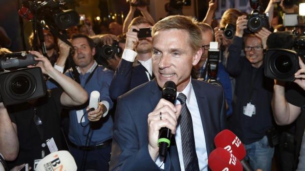 Politiker im dunkelblauen Anzug hält ein Mikrofon in der Hand und wird von Menschen mit Kameras und Fotoapparaten umringt.