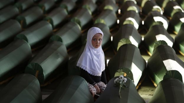 Ein muslimisches Mädchen trauert um einen Angehörigen, der beim Massaker von Srebrenica getötet worden war.