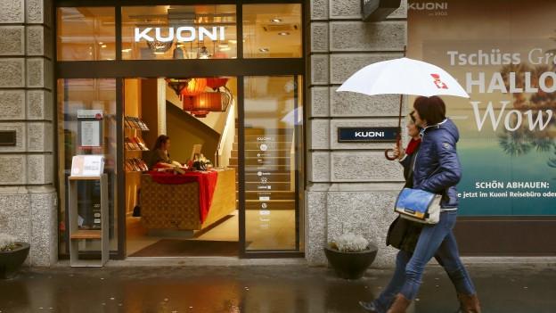 Zwei Frauen laufen in Zürich mit einem Regenschirm an einem Kuonigeschäft vorbei