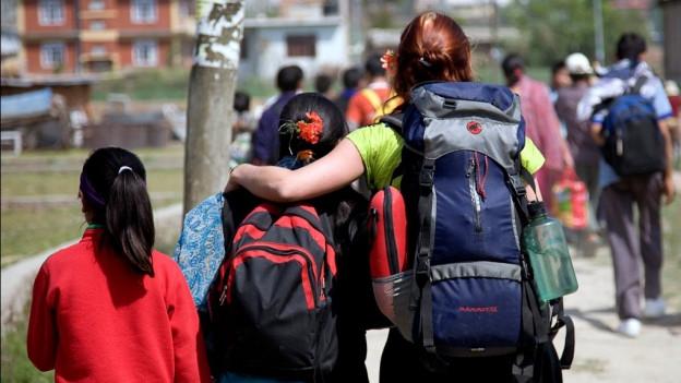 Freiwillige Helferin hält schützend Arm über ein Kind