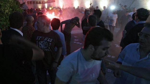 Demonstranten entzünden Pyros vor dem Parlament in Athen.