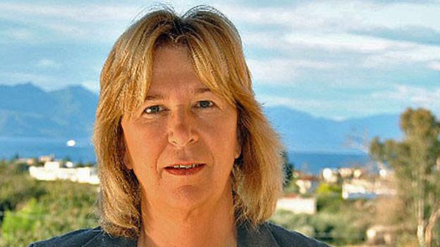 Portrait von Corinna Jessen - im Hintergrund ein griechisches Dorf und eine Bergkette.