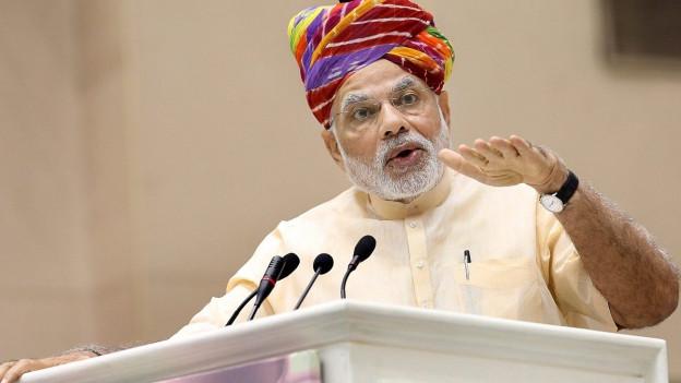 Das Bild zeigt Indiens Premier Narendra Modi hinter einem Rednerpult mit mehreren Mikrofonen.