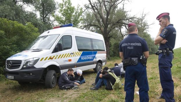 Auf dem Bild sind zwei ungarische Polizisten zu sehen, vor einer Gruppe von Einwanderern an der Grenze zu Serbien (23. Juni 2015).