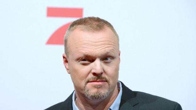 Auf dem Bild ist der deutsche TV-Tausendsassa Stefan Raab zu sehen vor dem Logo des Fernsehsenders Pro7.