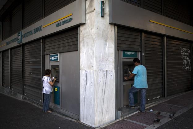 Griechinnen und Griechen heben am Sonntag an einem Automaten in Athen Geld ab.