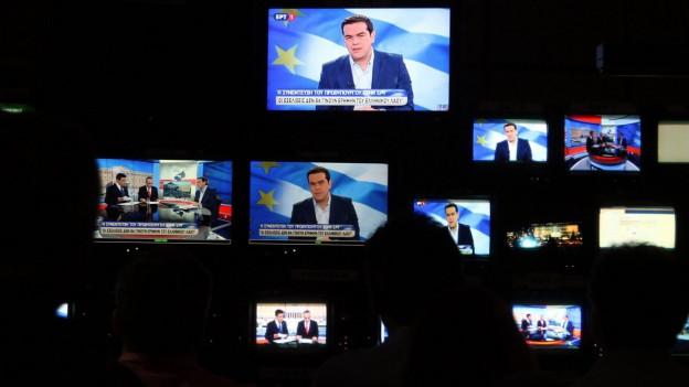 Merhere Fernsehbildschirme zeigen Ministerpräsident Tsipras bei seiner Rede.