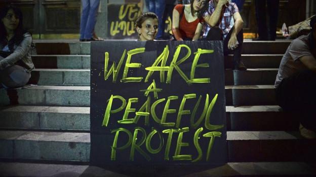 Eine Demonstrantin hält ein Plakat in den Händen.