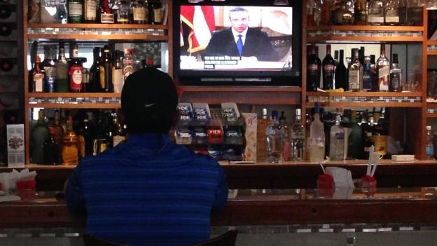 Ein Mann sitzt in einer Bar vor einem Fernsehbildschirm.