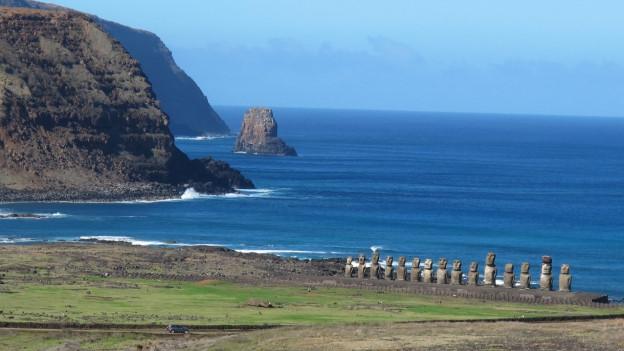 Blauer Himmel, blaues Meer, grüne Küste mit fünfzehn Steinstatuen.