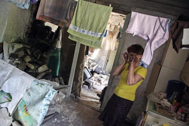 Frau schaut auf zerstörtes Haus in Ostukraine