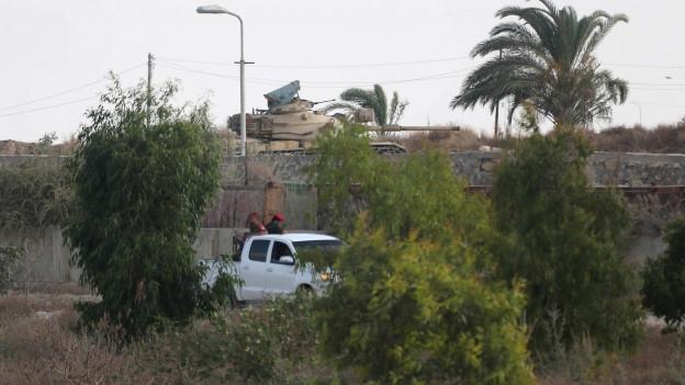 Das Bild zeigt einen Panzer hinter einer Mauer