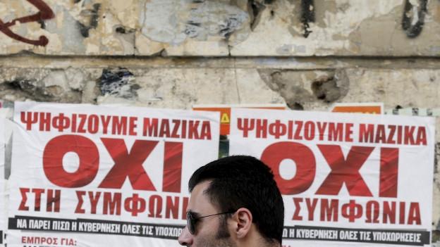 Mann mit Sonnenbrille läuft vor einer Mauer durch, ander Mauer hängen Plakate zur Referendumsabstimmung. Die fordern «oxi», also nein.
