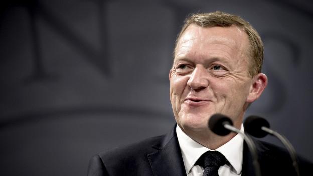 Lars Loekke Rasmussen im grauen Anzug und weissen Hemd vor einem grauen Hintergrund.