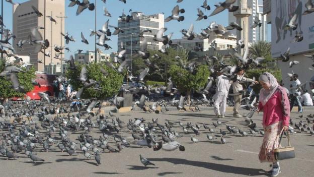 Eine Frau vor auffliegenden Tauben in Kuwait Stadt.