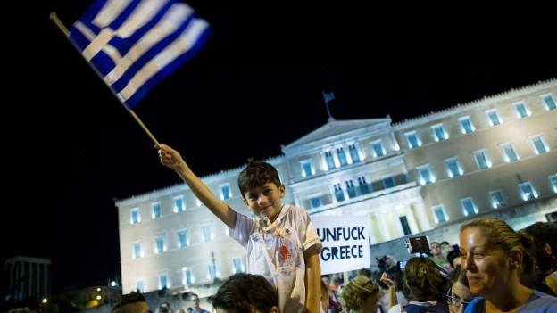 Auf dem Bild sind jubelnde Anhänger der Syriza-Partei vor dem Parlament in der Hauptstadt Athen zu sehen. Ein kleiner Junge schwenkt eine Griechenlandfahne.