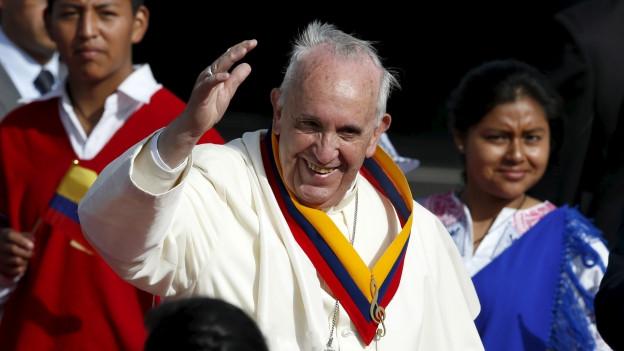 Papst Franziskus lächelt und hebt die rechte Hand zu einem Gruss. Um ihn herum sind mehrere Menschen zu sehen.