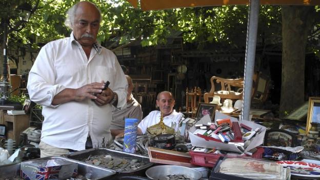 Ein Mann steht vor mehreren Behältern mit Drachmen.