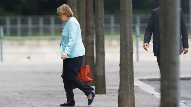 Die deutsche Bundeskanzlerin Angela Merkel überquert einen Platz..