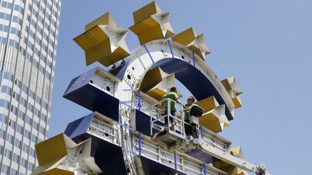 Arbeiter arbeiten an den Sternen der Euro-Skulptur vor der EZB.
