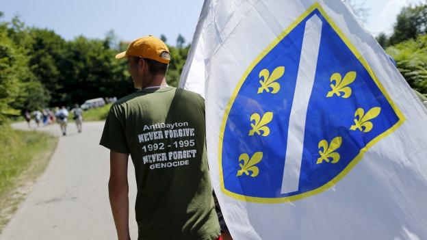 Das Bild zeigt einen Mann auf dem Friedensmarsch nach Srebrenica mit einer bosnischen Flagge über der Schulter.