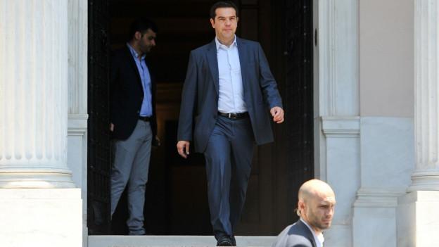 Alexis Tsipras schreitet durch eine Tür