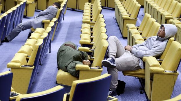 Journalisten hatten in Brüssel eine kurze Nacht. Hier zu sehen: Schlafende Medienleute zwischen Bänken in einem leeren Saal.